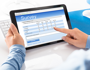 Hands holding a tablet computer and completing a survey