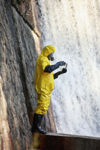Scientist standing near waterfalls and wearing protective clothing.