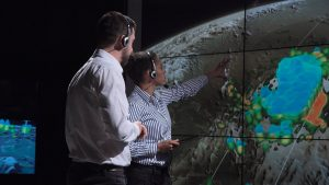Two meteorologists tracking a storm with satellite images.
