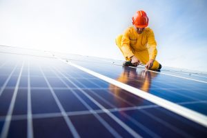 Person wearing protective clothing installing solar panels.